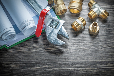 Adjustable spanner plumbing pipe connectors rolled construction plans water valve notebook pen.