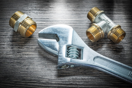 Adjustable wrench threaded pipe fittings on wooden board.