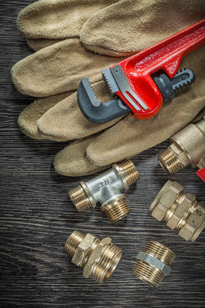 Safety gloves plumbing pipe wrench fittings water valve on wooden board.