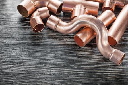 Raccords de tuyauterie d'eau en cuivre de plomberie sur planche de bois.