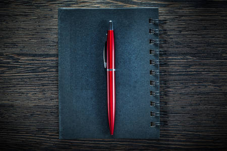 Black notepad pen on vintage wooden board directly above. Stock Photo