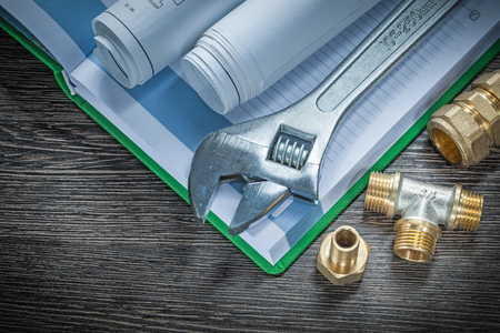 Adjustable spanner plumbing pipe connectors rolled construction plans notebook.