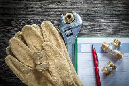 Adjustable spanner threaded pipe connectors leather protective gloves notepad pen.