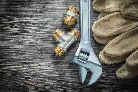 Adjustable wrench threaded pipe fittings safety gloves on wooden board.