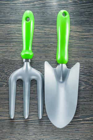 Gardening trowel fork hand spade on wooden board.