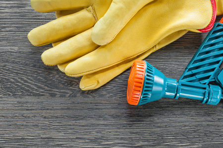 Garden hand spray gun protective gloves on wooden board.