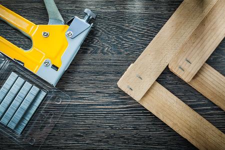 Le pistolet agrafeur de construction agrafe les planches de bois. Banque d'images