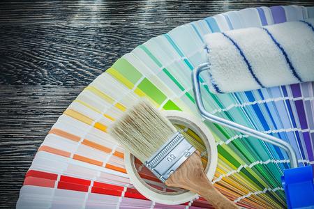 Paint brushes roller color pantone fan household tape on wood board. Foto de archivo