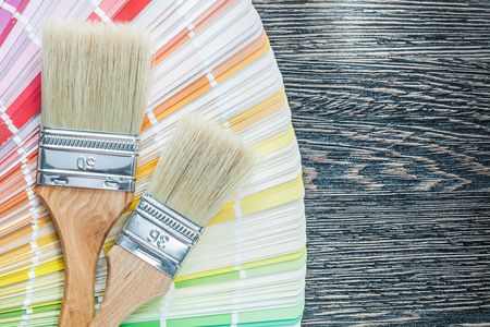 Color palette paint brushes on wooden board.