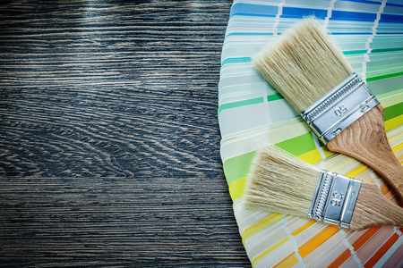 Paint brushes color pantone fan on wood board.