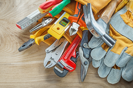 Tools in leather building belt on wooden board top view. Stock Photo