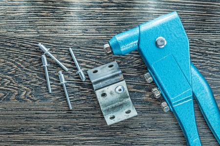 Pince à riveter rivets vis sur planche de bois.