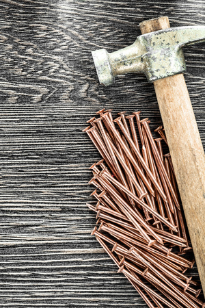 Stack of copper nails claw hammer on wooden board.