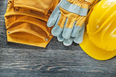Leather tool belt building helmet safety gloves on wooden board.