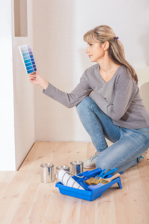 a young female sitting on floor near the wall selecting color with palette. Stock Photo