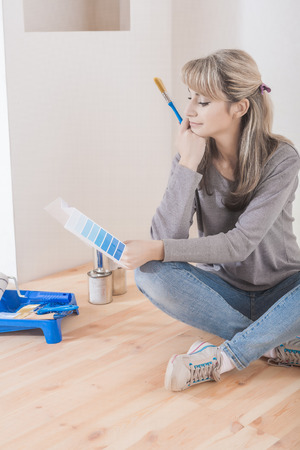 a beautiful female sitting on floor with sampler and paint brush selecting color.