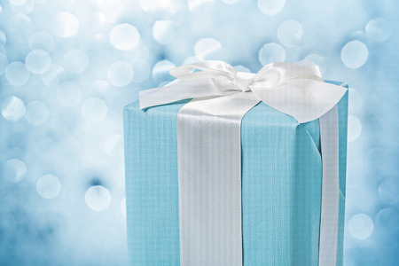 close up view blue gift box with white bow on blurred background.