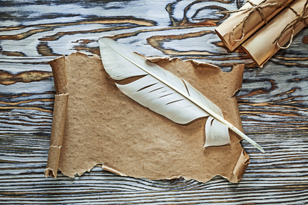 Vintage paper rolls parchment quill on wooden board.