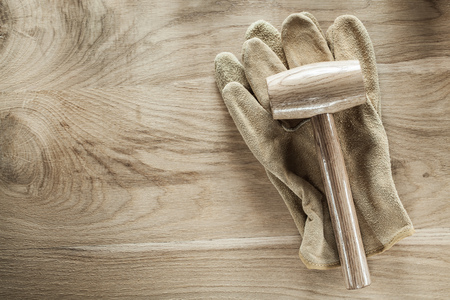 Safety gloves lump hammer on wooden board. Stock Photo