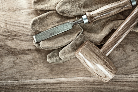 Lump hammer flat chisel protective gloves on wood board.