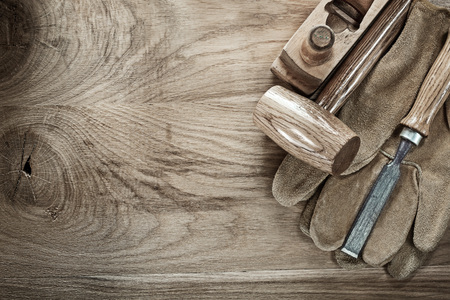 Wooden mallet shaving plane chisel protective gloves on wood board. Stock Photo