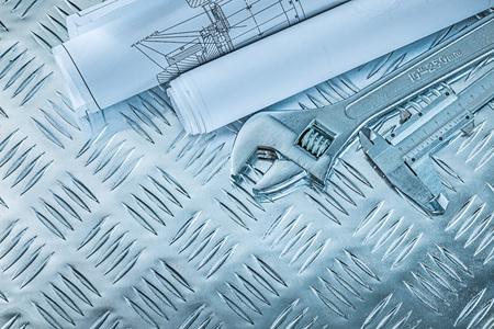 Vernier caliper construction plans adjustable spanner on channeled metal background.
