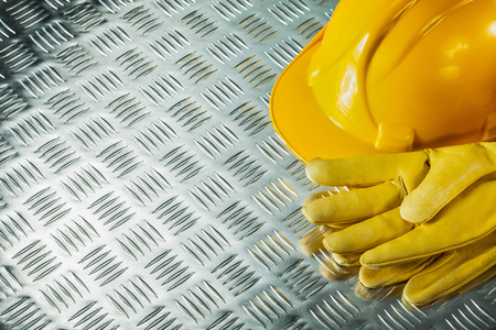 Leather safety gloves hard hat on fluted metal texture. Stock Photo
