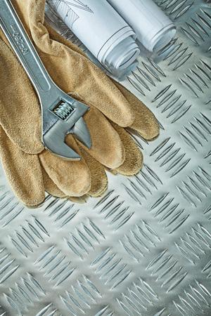Blueprints adjustable spanner protective gloves on fluted metal sheet. 版權商用圖片