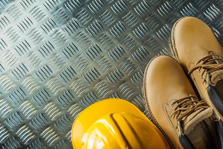 Waterproof boots hard hat on corrugated metal sheet.