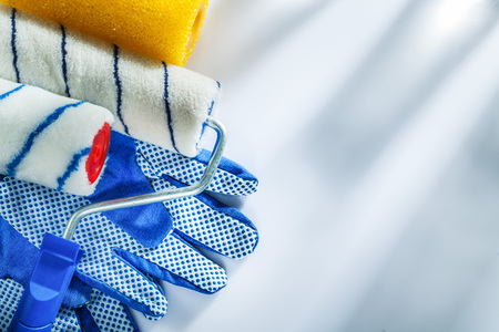 Pair of protective gloves paint rollers on white background. Stock Photo