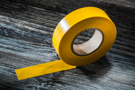 Yellow duct tape on vintage wooden board. 免版税图像