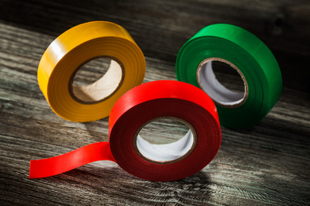 Set of rolled duct tapes on vintage wooden board.