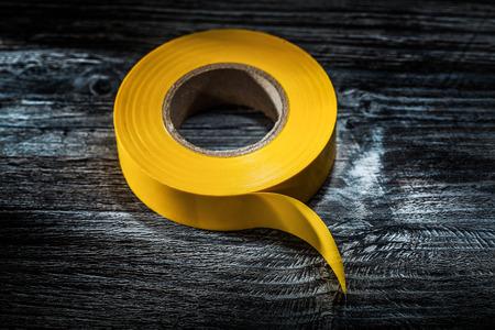 Yellow electrical tape on vintage wooden board. Zdjęcie Seryjne