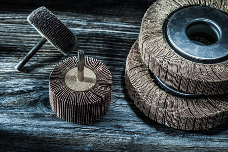Used rotary polishing flap wheels on vintage wooden board.