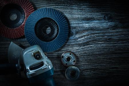 Angle grinder radial sanding discs on vintage wooden board.