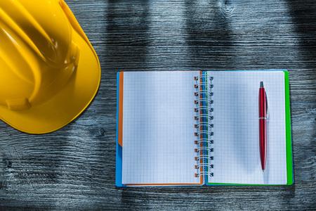 Notepad pen building helmet on wooden board. Reklamní fotografie
