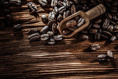 Fresh coffee seeds in scoop on wooden board.