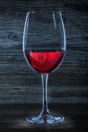wineglass with red wine on wood vertical view Stock Photo