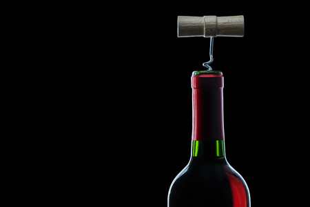 corckscrew in bottle of red wine on black background