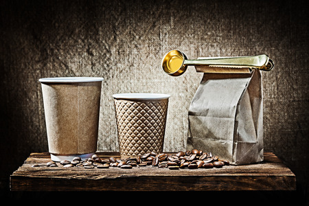 two papr cups and bag with coffee spoon beans