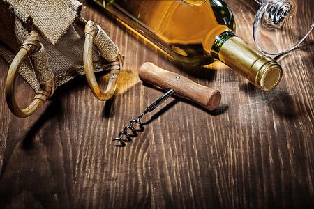 bottle of white wine burlap bag corckscrew glass