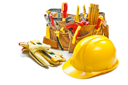 helmet gloves and construction tools in tool belt isolated on white