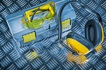 toolbox earphones and goggles on corrugated metalc sheet Stock Photo