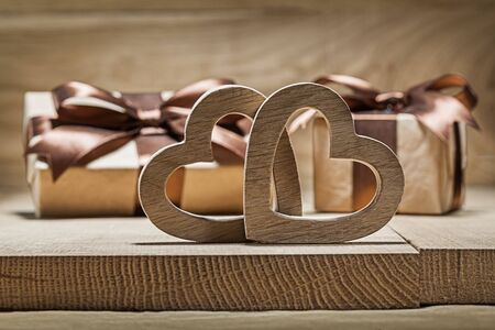 two wooden hearts and giftboxes on wood Imagens