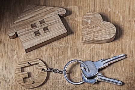 trinket house with keys and heart on wood background