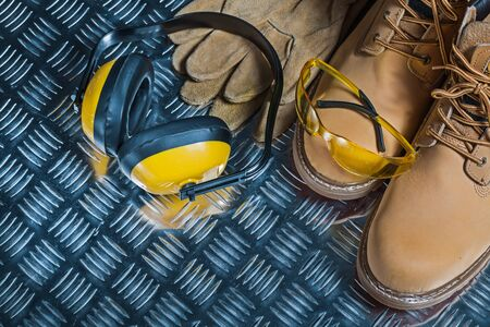 working boots yellow earphones and goggles on metalic sheet