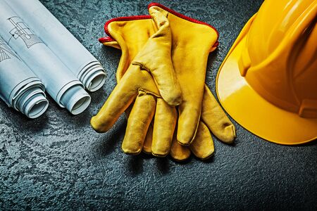 working gloves with yellow helmet and rolled blueprints