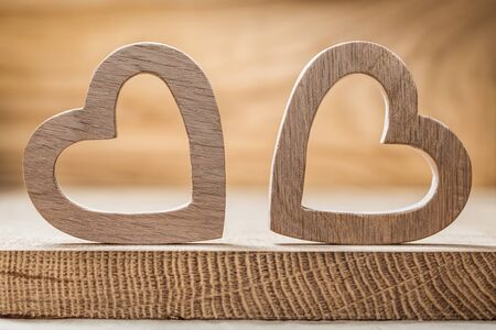two wooden  hearts on wood background close up view