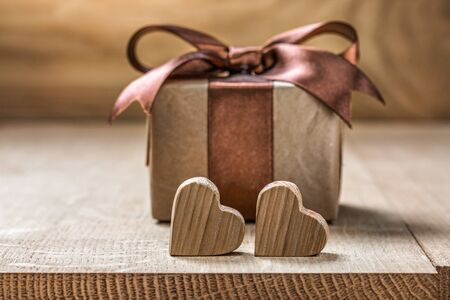 two very little wooden hearts and vintage  gift box on wood background