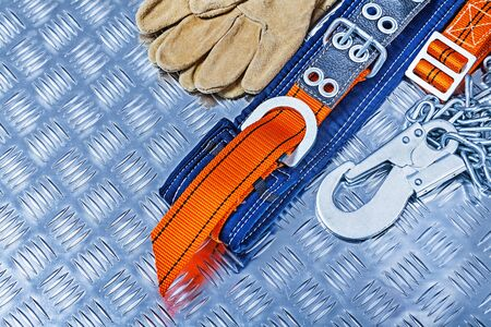 construction tools safety harness  and gloves on corrugated sheet of metall